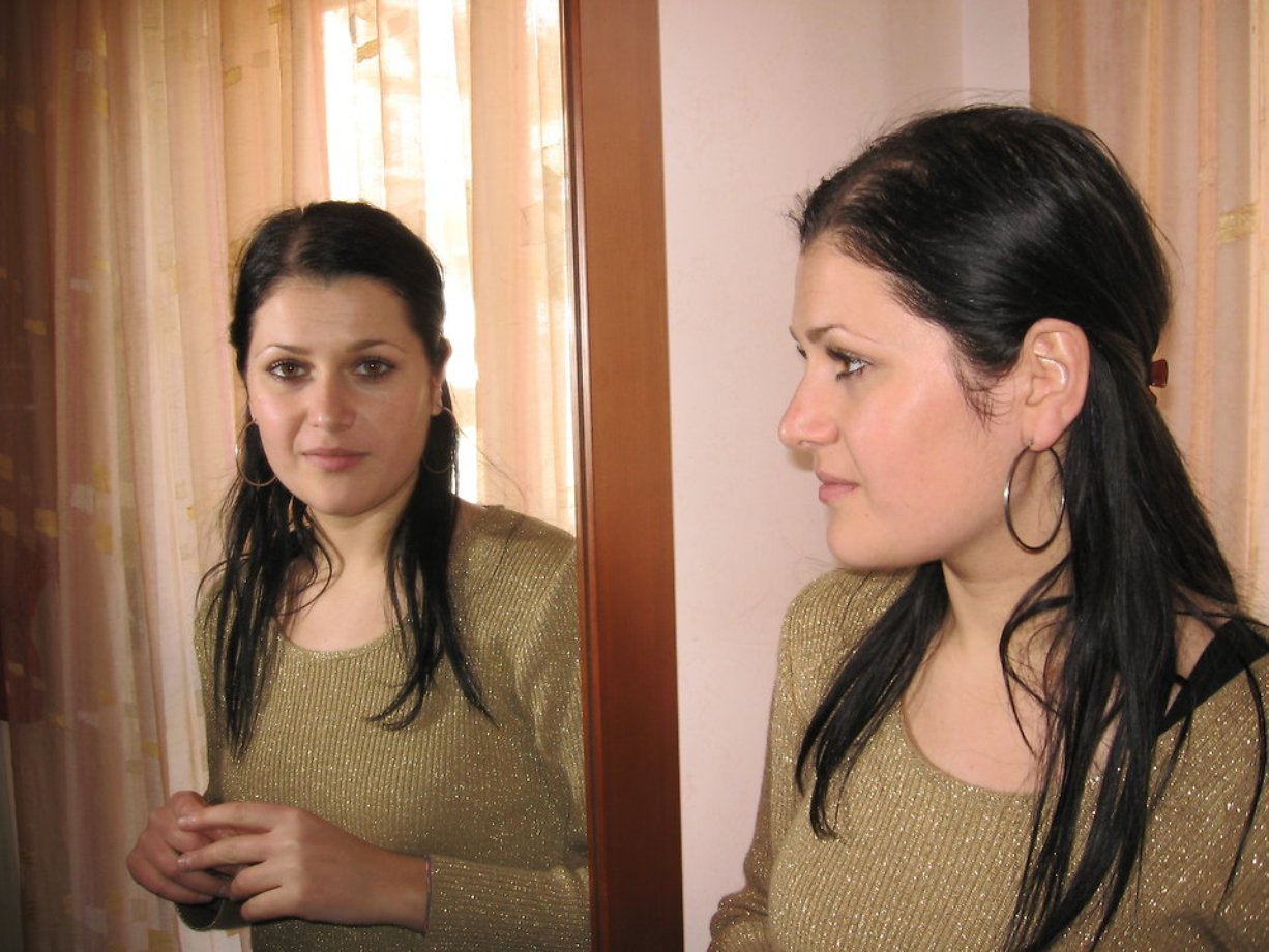 woman feeling insecure in a relationship looking at herself in a mirror