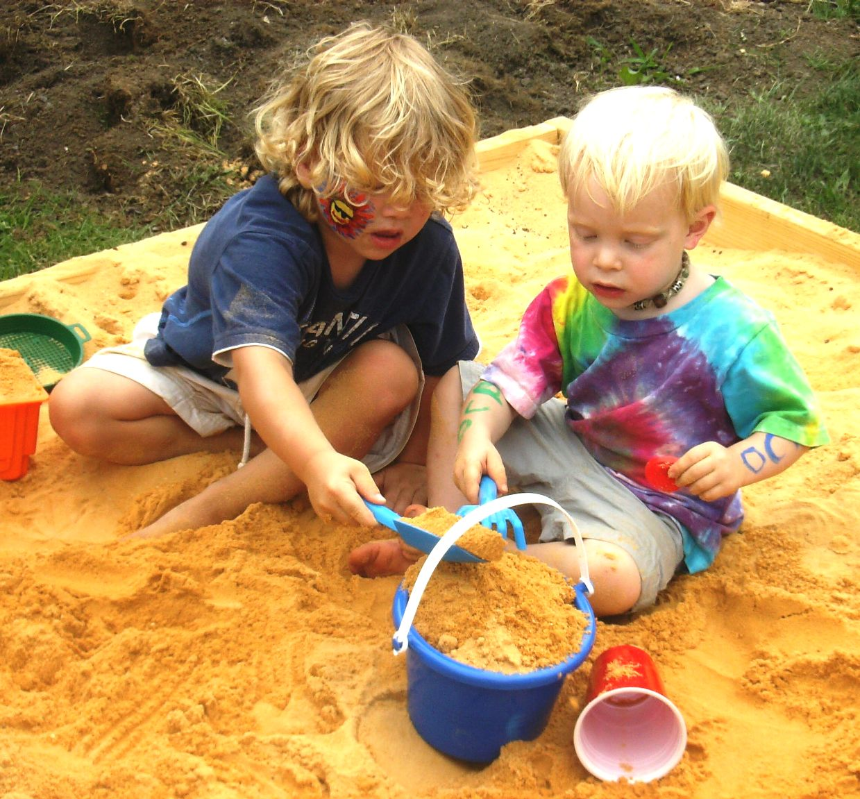 Relationship happiness illustrated by children playing in a sandbox.